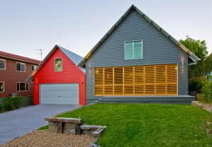 Sarris Beach House - steep pitched barn like roof with colourful gables beach house - timber louvre bifold doors