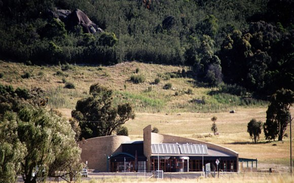 Tidbinbilla Visitors Centre -distant view double curved mud brick walls autonomous building