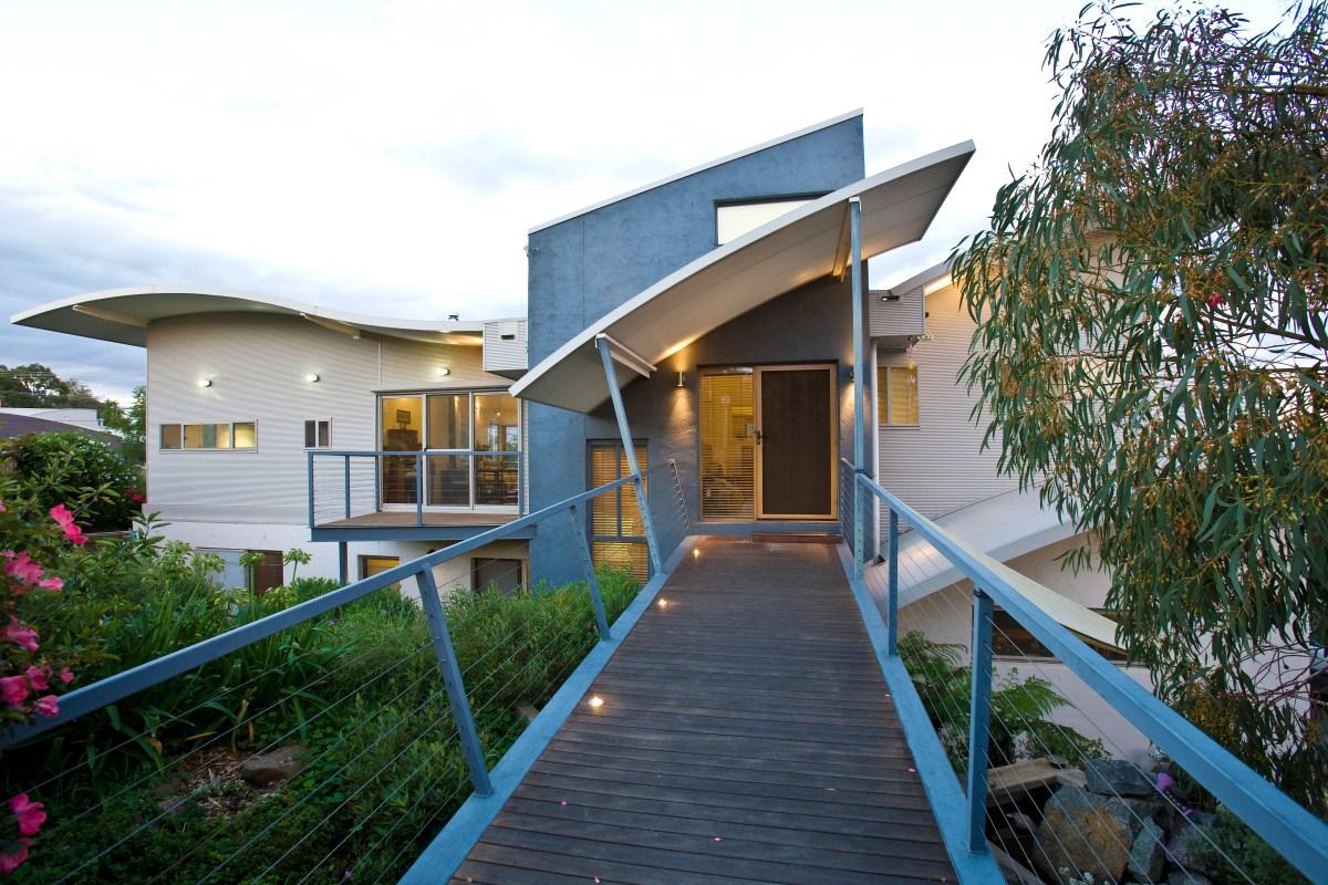 Bushfire House - bridge to entry at upper level - curved Ritek roof