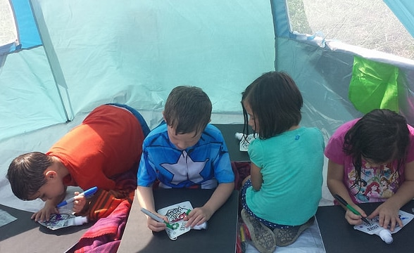 Children decorate reusable water pouches while sitting in the shade of a tent canopy.