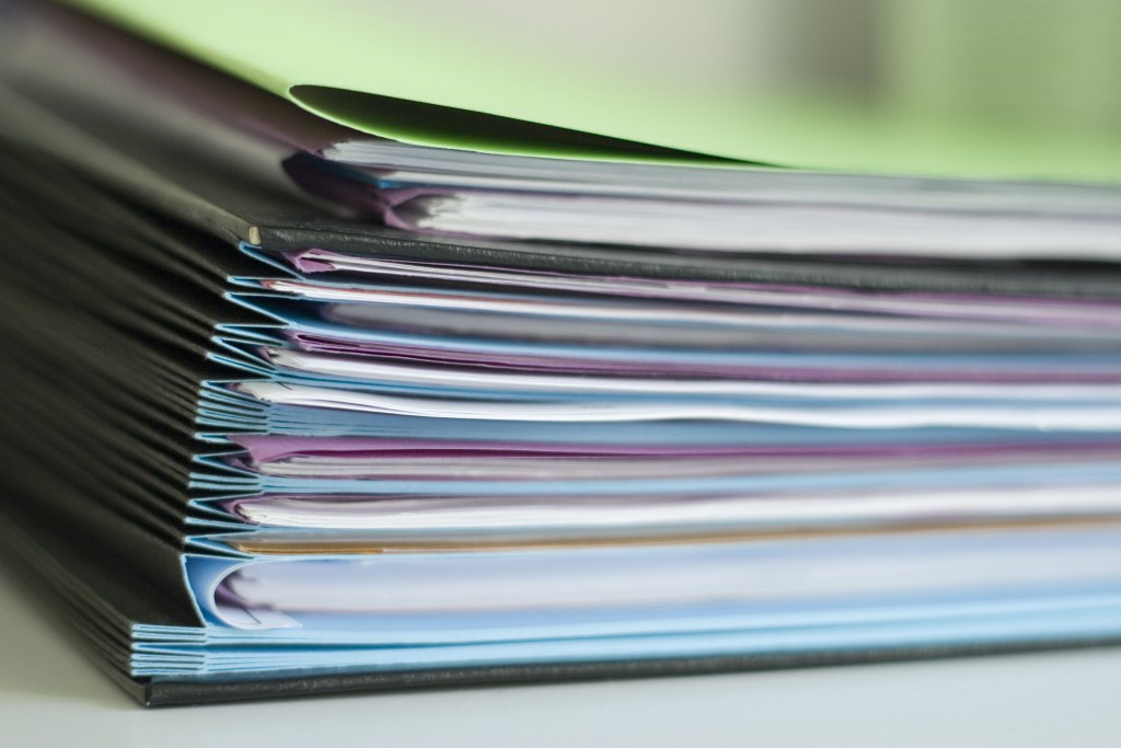 Medtech dossiers in colorful file folders stacked neatly.