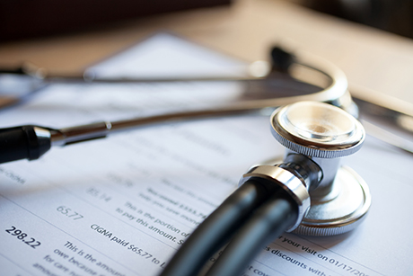 Stethoscope sitting on a clipboard showing payer reimbursement for a medical device.