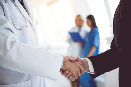 Doctor shaking hands with medical society board member.