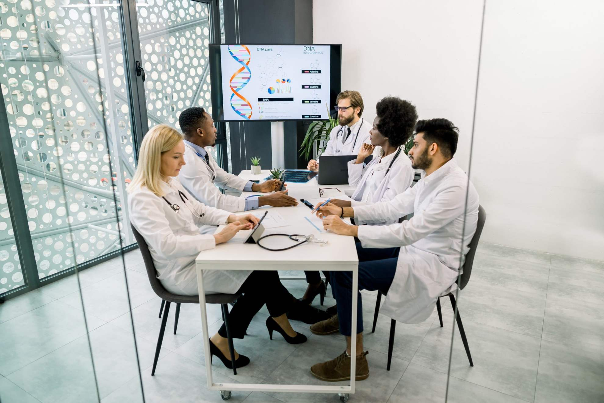 Team of scientists designing a clinical trial at a conference table.