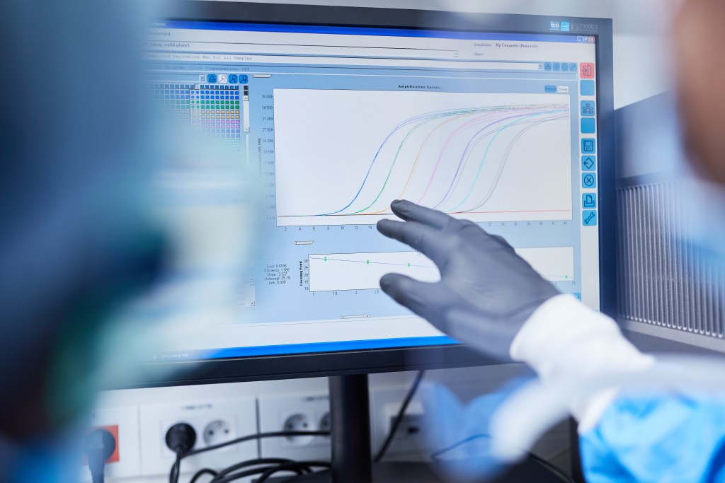 Computer monitor showing various data and graphs, gloved hand of a scientist pointing at data chart.