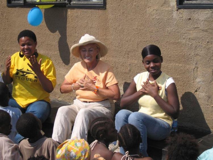 Linda Tellington Jones teaches orphans in Soweto how to do ttouch heart hugs