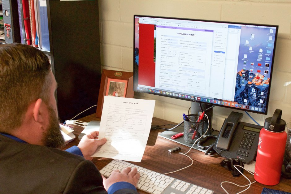 Keith Frost is filling out a travel application from his student teacher evaluation in Slaton, Texas.