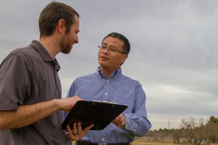 [Left to Right] Joey Young Ph. D., and Wenxuan Guo Ph. D., look over plans and data for their turfgrass research.