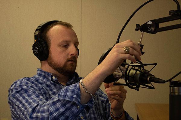 John adjusting his podcast recording equipment.