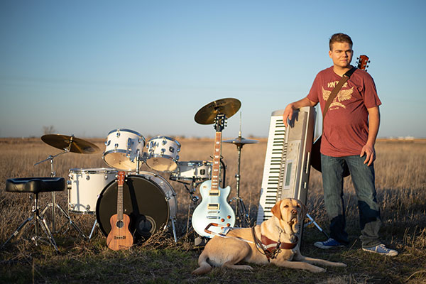 Caleb Snapp with his instruments and service dog, Grit.