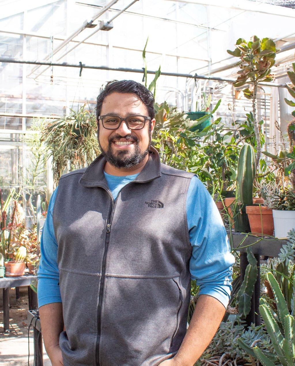 Photo of Vikram Baliga standing in the greenhouse.