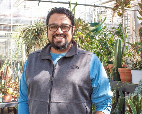 Photo of Vikram Baliga standing in the greenhouse.