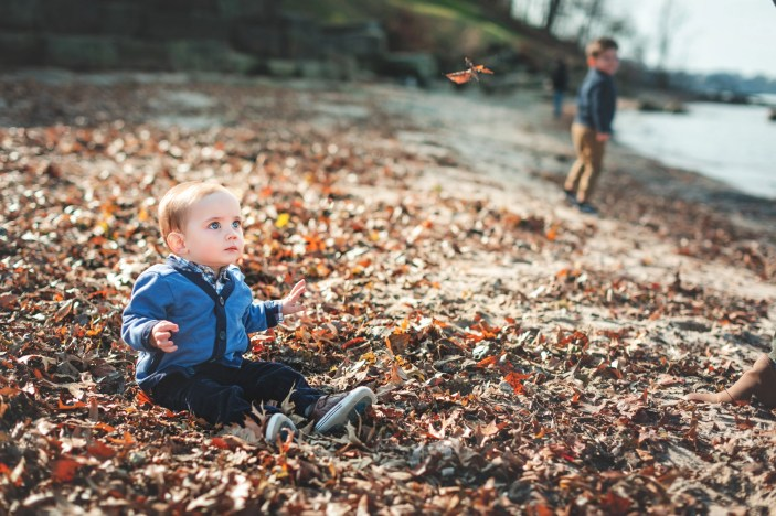 baby playing in leaves at rocky river park