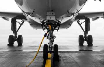 gray air vehicle with yellow coated cable around docking wheels