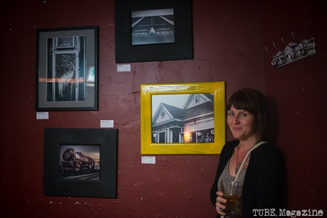 """Artist Sarah Elliott amongst her photographs hanging at """"The Wall"""" at The Hideaway located in Sacramento CA. May 2015. Photo Melissa Uroff"""