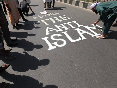 """Mann pinselt Slogan """"Hang the Anti-Islam"""" auf eine Straße in Dhaka, Bangladesch"""