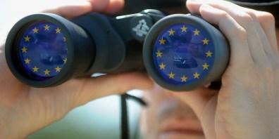 Ein Mensch schaut durch ein Fernglas in dem sich EU-Fahnen spiegeln