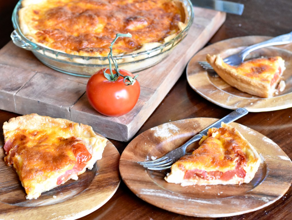 A dinner table set with a large tomato pie, browned on top. And three slices of tomato pie on wooden plates surrounding it.