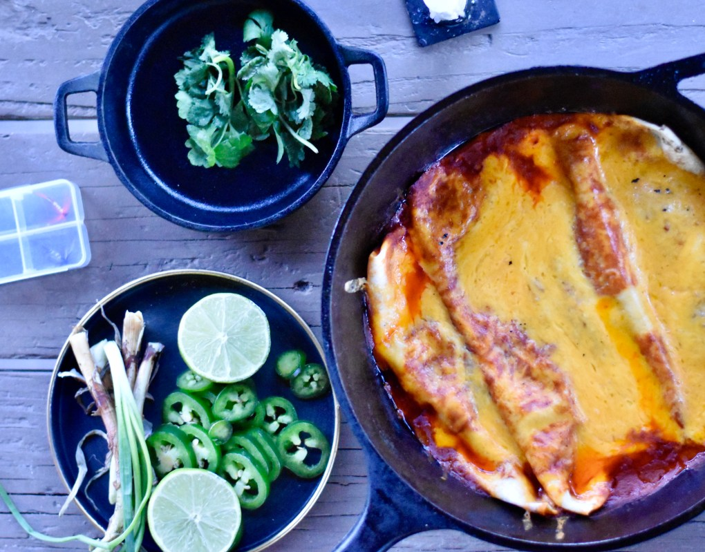An overhead shot of a camping meal, including two cast iron pans, one with cilantro garnish, one with a very cheesy enchilada plate hot off the grill. A dish of jalapeños, green onions and limes ready for garnish is nearby. Finally, a box of fishing flies can be seen far left.