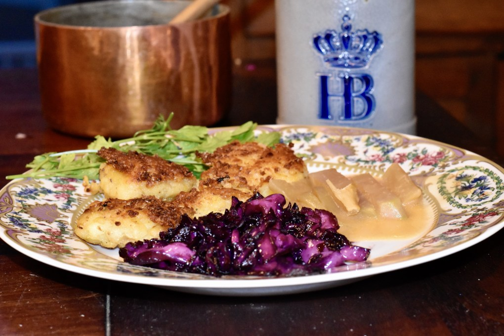 An ornate plate with a german meal, purple red cabbage in the front, kohlrabi in white sauce on the right, and potato frikadellen on the left. Behind slightly out of focus is a copper pot with a wooden spoon and a Bierstein that says HB