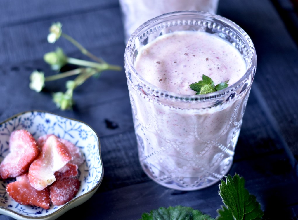 Close up of a home-grown strawberry made smoothie with whole strawberries close by