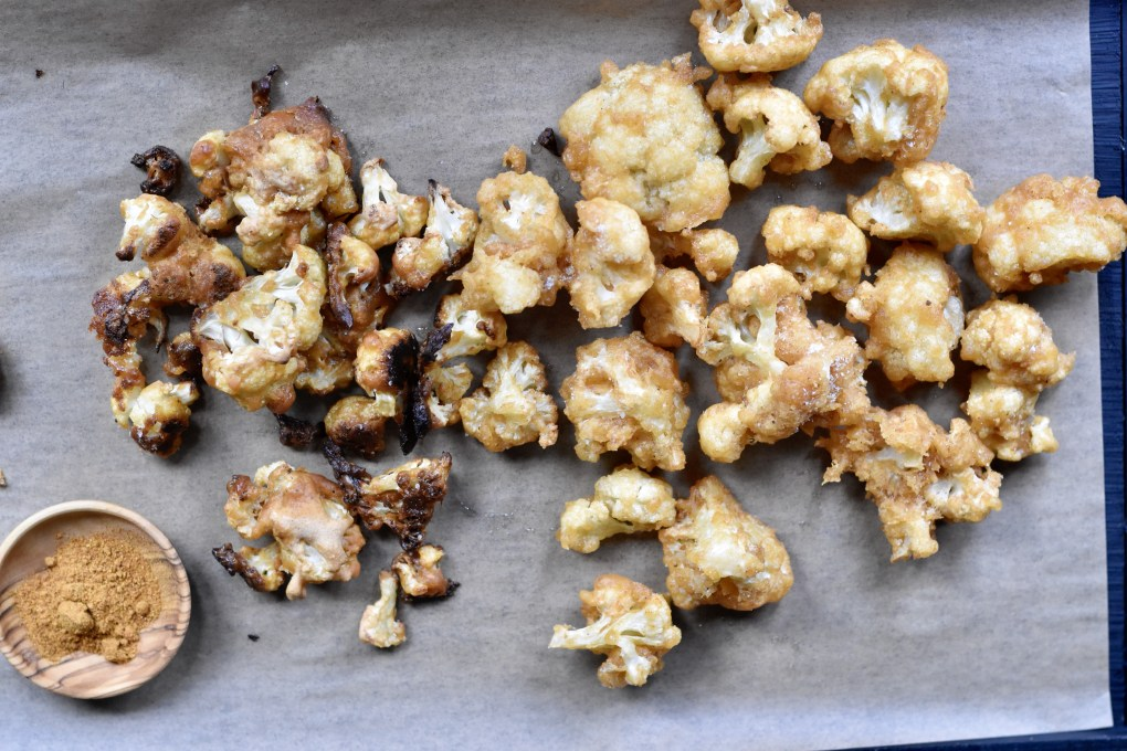 A tray of roasted and fried cauliflower. With a small wooden bowl with paprika spice. Displayed on a parchment baking  sheet.
