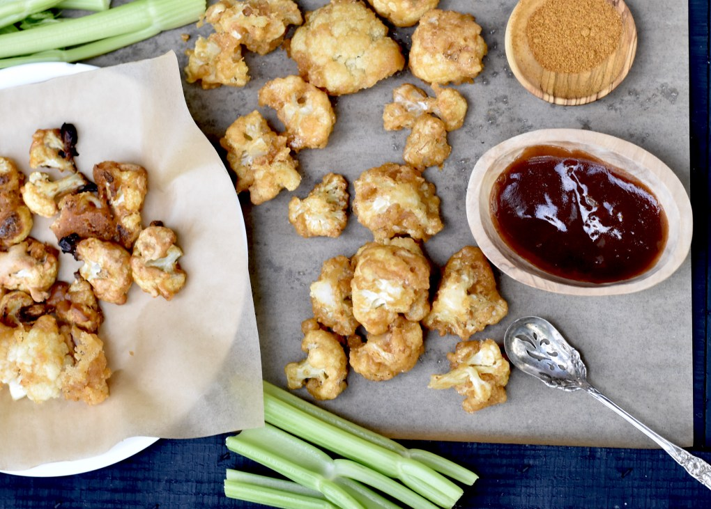 Overhead shot of beer battered cauliflower bites with a healthy side of BBQ sauce