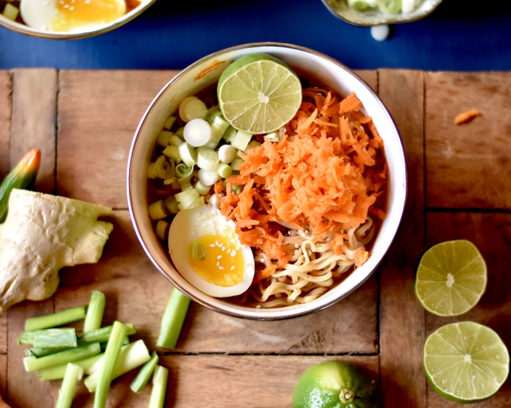 A bowl of ramen with shredded carrots, a soft boiled egg, scallions and a lime.