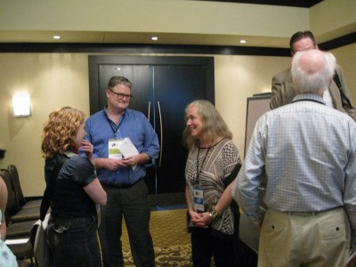 Nigel Beale chatting with poet Susan McMaster and other attendees