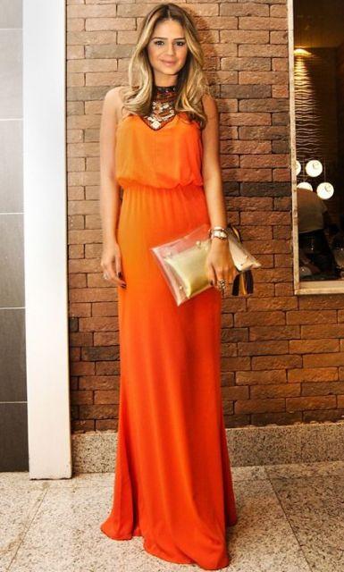 vestido longo laranja elegante com bolsa dourada