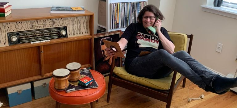 """Michelle at home holding a vintage telephone and 7"""" record"""