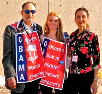 L to R: Craig Downer, Lady Advocate, Elyse Gardner at Las Vegas rally earlier this year wearing protest signs.