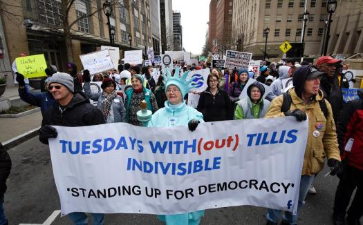Tuesdays with Tillis Marches in HKonJ. Lady Liberty and other members carrying a banner on Fayetteville Street.