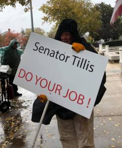Tuesdays with Tillis marcher at Senator Thom Tillis office. Sign says Senator Tillis, Do Your Job.