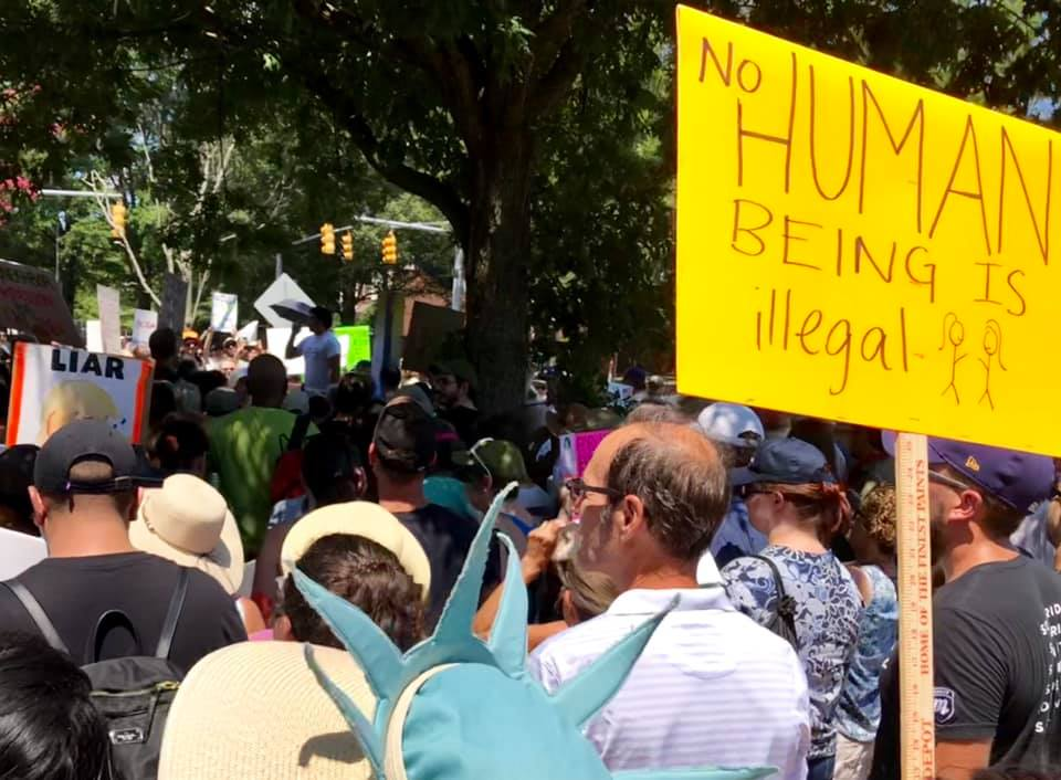 Protesters in front of Thom Tillis' office protesting the separation of families at the border. Yellow sign reads No Human Beings are Illegal