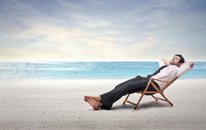 Man sitting on a beach in his dress shirt and tie