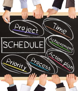 Photo of business hands holding blackboard and writing SCHEDULE diagram