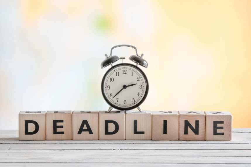 Clock on a deadline sign at a wooden desk