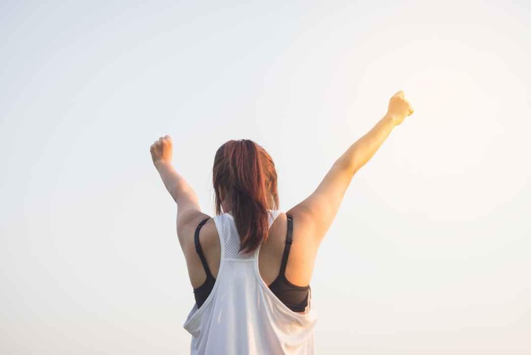 Woman raising both hands on top
