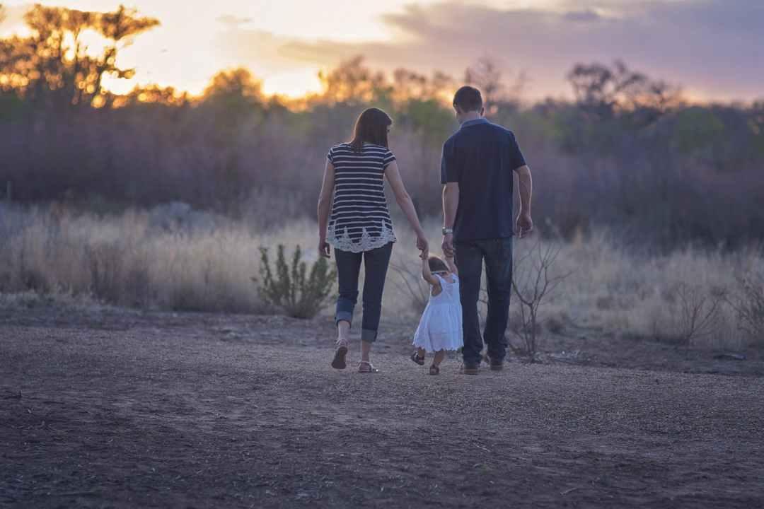 Family of three walking on grassy field