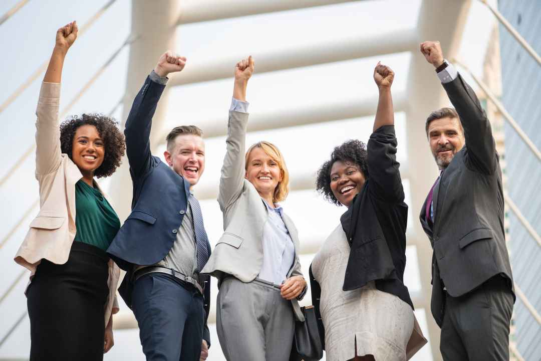 A group of employee standing and raising their arm