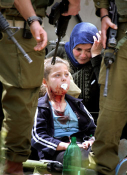 Israeli soldiers stand around a Palestinian injured girl, after she was shot by an Israeli soldier in the al-Fawwar camp, near Hebron