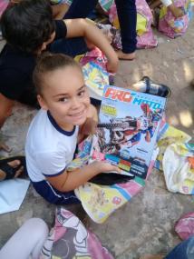 Criança com revista doada pelo projeto (Divulgação)