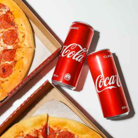 coca cola cans beside pizza