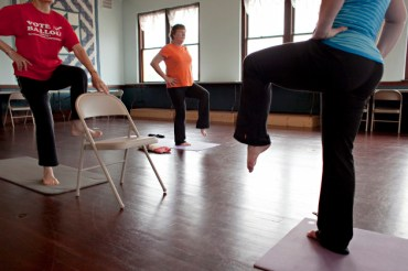Lois Brenner of rural Randall, from left to right, Jean Clark of Little Falls, and instructor Kristie Roach move into tree pose during a yoga class on June 4, 2013. Yoga classes are held Tuesday and Thursday mornings in a second floor studio space at The Old Creamery Quilt Shop in Randall. The 1,200-square-foot room is used for classes and workshops and is also available for rent. (Ann Arbor Miller for MPR)
