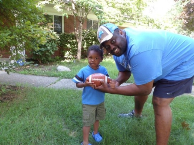 Courtney Conover guest contributor for Tuned In Parents shares her view on youth football - photo of her son Scottie with dad Scott Conover