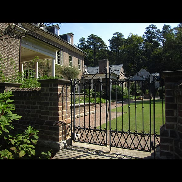 Brick pier and iron gate at an Atlanta residence, landscape designed by Tunnell and Tunnell Landscape Architecture.