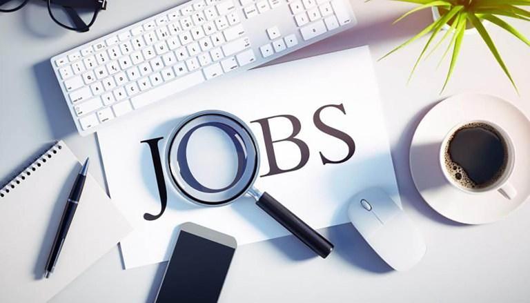 Mise en scène d'une recherche d'emploi avec une loupe sur le mot JOB pour illustrer l'article sur les Jobs d'été du site de la mairie de tupin et semons www.tupinetsemons.fr