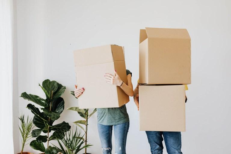 Photo de 2 personnes, un homme et une femme portant des carons de déménagement pour illustrer la page parc immobilier locatif de la commune de Tupin et semons sur le site www.tupinetsemons.fr