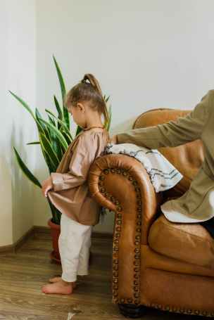 little girl near crop parent on sofa at home